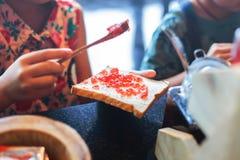 De Aardbeijam die van de handgietlepel voor ontbijt maakt royalty-vrije stock foto