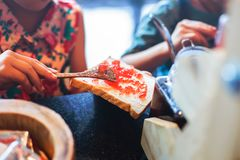 De Aardbeijam die van de handgietlepel voor ontbijt maakt royalty-vrije stock afbeeldingen
