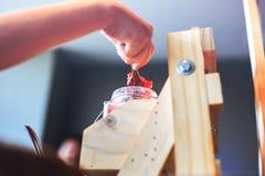 De Aardbeijam die van de handgietlepel voor ontbijt maakt royalty-vrije stock fotografie