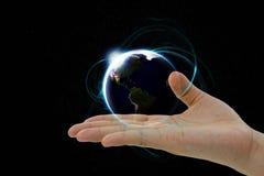 De aardeplaneet die over de hand hangen Stock Foto's