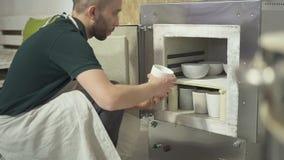 In de aardewerkworkshop zet de mens kleipotten voor vuren in de oven stock videobeelden