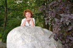 De aardige vrouw van gemiddelde jaren bevindt zich achter een reusachtige kei in het park Royalty-vrije Stock Foto