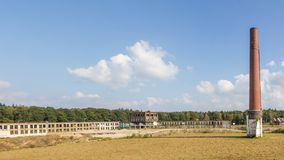 De Abadoned industriële bouw met een hoge schoorsteen Stock Afbeeldingen