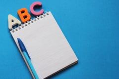 De abc-eerste brieven van het Engelse alfabet op een blauwe achtergrond Notitieboekje en Pen Lege ruimte voor tekst De idylle van stock foto's