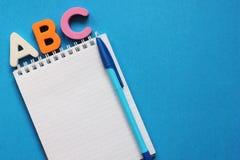 De abc-eerste brieven van het Engelse alfabet op een blauwe achtergrond Notitieboekje en Pen Lege ruimte voor tekst De idylle van royalty-vrije stock afbeelding