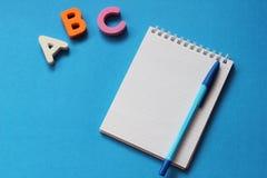 De abc-eerste brieven van het Engelse alfabet op een blauwe achtergrond Notitieboekje en Pen Lege ruimte voor tekst De idylle van royalty-vrije stock foto
