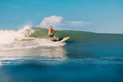 12 de abril de 2019 Bali, Indonesia Lev?ntese el paseo de la persona que practica surf de la paleta en ola oce?nica Lev?ntese la  fotografía de archivo libre de regalías