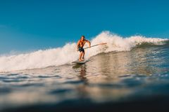 12 de abril de 2019 Bali, Indonesia Lev?ntese el paseo de la persona que practica surf de la paleta en ola oce?nica Lev?ntese la  foto de archivo