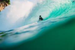 23 de abril de 2018 Bali, Indonesia Paseo de la persona que practica surf en onda grande del barril en Padang Padang El practicar Imagen de archivo
