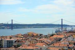 25 de Abril Bridge och Alfama, Lissabon, Portugal Royaltyfria Bilder