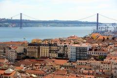 25 de Abril Bridge och Alfama, Lissabon, Portugal Royaltyfri Foto