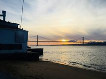 Sunset in. The 25 de Abril Bridge is a suspension bridge connecting the city of Lisbon, capital of Portugal, to the municipality of Almada on the left bank of royalty free stock photos
