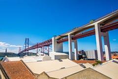 25 DE Abril Bridge zijn een brug die de stad van Lissabon verbinden met de gemeente van Almada op de linkeroever van de Tejo-rivi Stock Fotografie