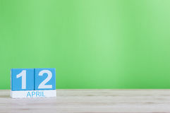 12 de abril Día 12 de mes, calendario en la tabla de madera y fondo verde Tiempo de primavera, espacio vacío para el texto Imagen de archivo libre de regalías