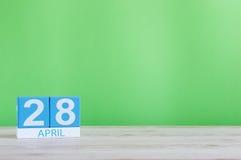 28 de abril Día 28 de mes, calendario en la tabla de madera y fondo verde Tiempo de primavera, espacio vacío para el texto Foto de archivo libre de regalías
