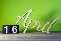 16 de abril Día 16 de mes, calendario en la tabla de madera y fondo verde Tiempo de primavera, espacio vacío para el texto Foto de archivo