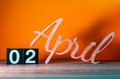 2 de abril Día 2 del mes, calendario de madera diario en la tabla con el fondo anaranjado Concepto del tiempo de primavera Fotos de archivo libres de regalías