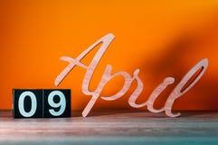 9 de abril Día 9 del mes, calendario de madera diario en la tabla con el fondo anaranjado Concepto del tiempo de primavera Fotos de archivo libres de regalías