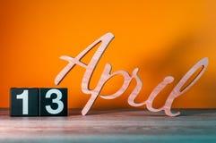 13 de abril Día 13 del mes, calendario de madera diario en la tabla con el fondo anaranjado Concepto del tiempo de primavera Imagen de archivo libre de regalías