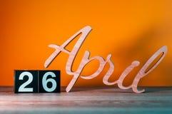 26 de abril Día 26 del mes, calendario de madera diario en la tabla con el fondo anaranjado Concepto del tiempo de primavera Imagen de archivo libre de regalías