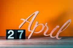 27 de abril Día 27 del mes, calendario de madera diario en la tabla con el fondo anaranjado Concepto del tiempo de primavera Imagen de archivo libre de regalías
