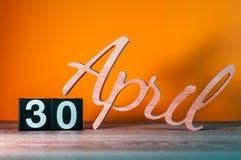 30 de abril Día 30 del mes, calendario de madera diario en la tabla con el fondo anaranjado Concepto del tiempo de primavera Foto de archivo libre de regalías