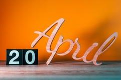 20 de abril Día 20 del mes, calendario de madera diario en la tabla con el fondo anaranjado Concepto del tiempo de primavera Imagen de archivo libre de regalías