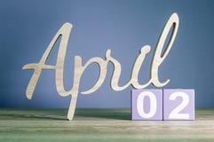 2 de abril Día 2 del mes, calendario diario en la tabla de madera con el fondo púrpura o violeta Tema del tiempo de primavera Imagen de archivo libre de regalías