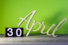 30 de abril Día 30 de mes, calendario en la tabla de madera y fondo verde Tiempo de primavera, espacio vacío para el texto Fotos de archivo libres de regalías