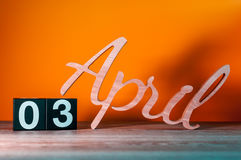 3 de abril Dia 3 do mês, calendário de madeira diário na tabela com fundo alaranjado Conceito do tempo de mola Imagens de Stock