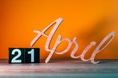 21 de abril dia 21 do mês, calendário de madeira diário na tabela com fundo alaranjado Conceito do tempo de mola Imagens de Stock