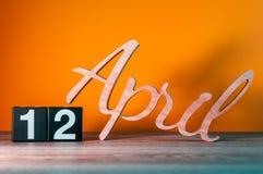 12 de abril Dia 12 do mês, calendário de madeira diário na tabela com fundo alaranjado Conceito do tempo de mola Foto de Stock Royalty Free