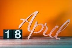 18 de abril dia 18 do mês, calendário de madeira diário na tabela com fundo alaranjado Conceito do tempo de mola Imagens de Stock