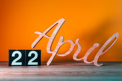 22 de abril Dia 22 do mês, calendário de madeira diário na tabela com fundo alaranjado Conceito do tempo de mola Fotografia de Stock