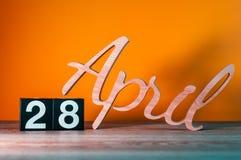 28 de abril Dia 28 do mês, calendário de madeira diário na tabela com fundo alaranjado Conceito do tempo de mola Fotografia de Stock