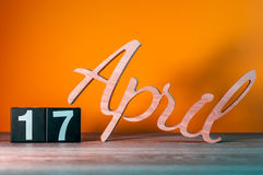 17 de abril Dia 17 do mês, calendário de madeira diário na tabela com fundo alaranjado Conceito do tempo de mola Fotografia de Stock