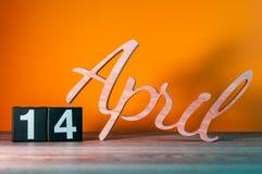 14 de abril Dia 14 do mês, calendário de madeira diário na tabela com fundo alaranjado Conceito do tempo de mola Imagens de Stock