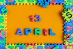 13 de abril Dia 13 do mês, calendário diário do enigma do brinquedo da criança no fundo alaranjado Tema do tempo de mola Fotos de Stock Royalty Free