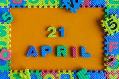 21 de abril dia 21 do mês, calendário diário do enigma do brinquedo da criança no fundo alaranjado Tema do tempo de mola Fotografia de Stock Royalty Free
