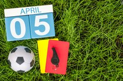 5 de abril Dia 5 do mês, calendário de madeira da cor no fundo da grama verde do futebol com equipamento do futebol O tempo de mo Imagens de Stock