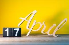 17 de abril Dia 17 do mês, calendário na tabela de madeira e fundo amarelo Tempo de mola, espaço vazio para o texto Fotografia de Stock
