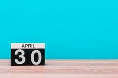 30 de abril Dia 30 do mês, calendário na tabela de madeira e fundo de turquesa Tempo de mola, espaço vazio para o texto Fotografia de Stock Royalty Free