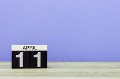 11 de abril Dia 11 do mês, calendário na tabela de madeira e fundo roxo Tempo de mola, espaço vazio para o texto Fotografia de Stock