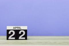 22 de abril Dia 22 do mês, calendário na tabela de madeira e fundo roxo Tempo de mola, espaço vazio para o texto Imagens de Stock Royalty Free
