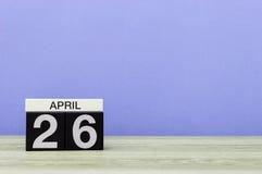 26 de abril Dia 26 do mês, calendário na tabela de madeira e fundo roxo Tempo de mola, espaço vazio para o texto Imagens de Stock