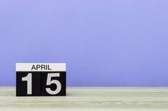 15 de abril Dia 15 do mês, calendário na tabela de madeira e fundo roxo Tempo de mola, espaço vazio para o texto Fotografia de Stock Royalty Free
