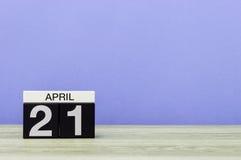 21 de abril dia 21 do mês, calendário na tabela de madeira e fundo roxo Tempo de mola, espaço vazio para o texto Fotografia de Stock