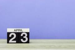 23 de abril Dia 23 do mês, calendário na tabela de madeira e fundo roxo Tempo de mola, espaço vazio para o texto Foto de Stock Royalty Free