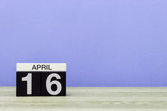16 de abril Dia 16 do mês, calendário na tabela de madeira e fundo roxo Tempo de mola, espaço vazio para o texto Imagens de Stock Royalty Free