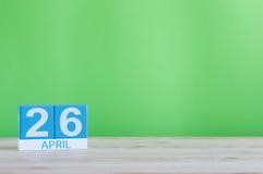 26 de abril Dia 26 do mês, calendário na tabela de madeira e fundo verde Tempo de mola, espaço vazio para o texto Fotos de Stock